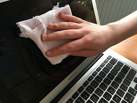 Wiping a laptop screen with a cloth