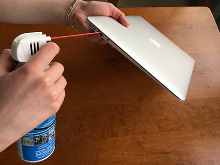 Using a can of compressed air to clean out a USB port on a laptop