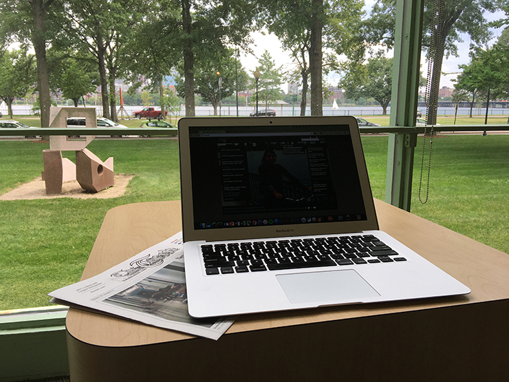 Laptop and a copy of The Tech in front of a window at Hayden Library overlooking the Charles River