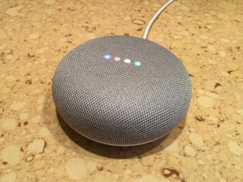 Picture of a Google Home Mini with four colored light on top lit up.
