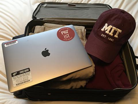 Picture of an Apple laptop with MIT stickers on it, next to a maroon baseball cap with MIT in white on it, both lying on an open suitcase.