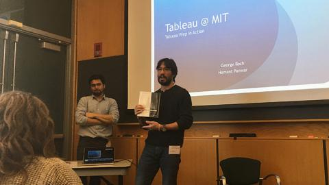 Man holding a book in front of a screen with the words Tableau at  MIT: Tableau Prep in Action.