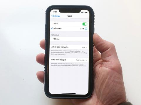 A hand holding an iPhone displaying the WiFi setting screen which shows it connected to the eduroam network.