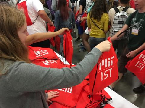 Woman handing out a bag that says MIT IS&T to students