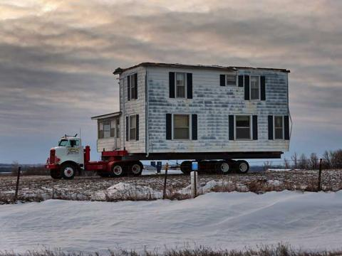 A small house being moved on the back of a truck