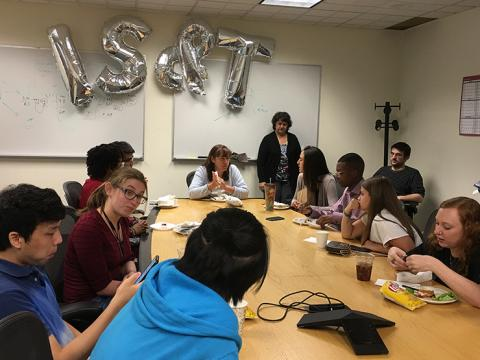 """Students eating lunch around a conference room table. Silver balloon letters spelling out """"IS&T"""" are floating against a wall in the background against a whiteboard."""