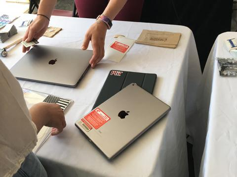 A laptop and tablet being tagged with STOP Theft tags