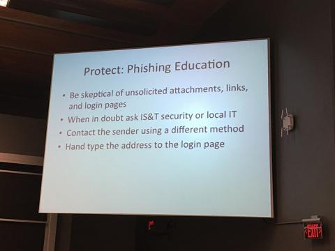 "Slide projected on a screen with the title ""Protect: Phishing Education."""