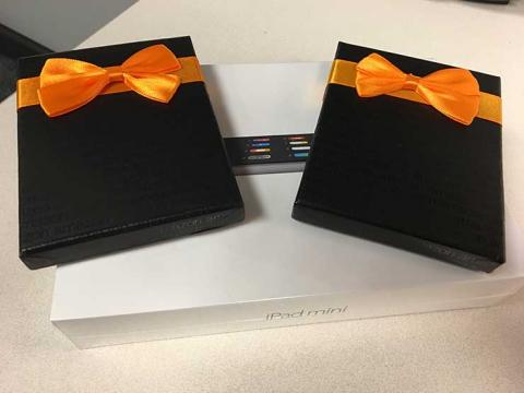 An iPad Mini and two Amazon gift boxes