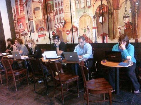 People working on laptops at a coffee shop