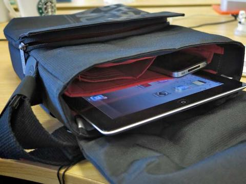 Open travel bag with a cell phone and tablet in it