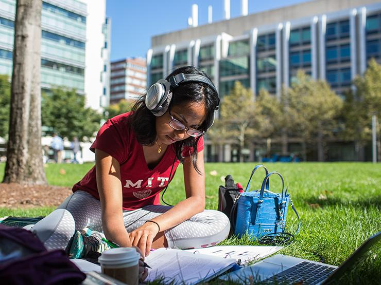 Female student wearing MIT t-shirt sitting on the grass studying