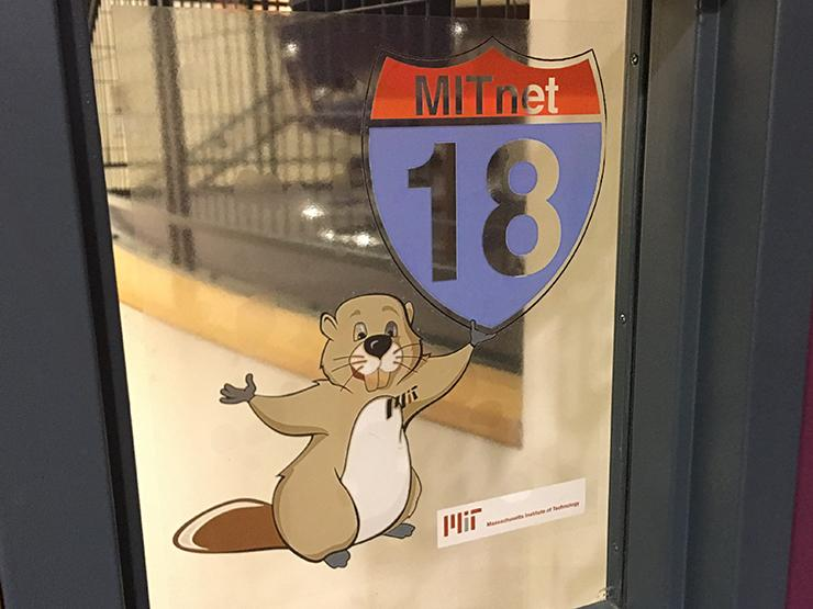 Sticker on a window of a beaver holding an MITnet 18 road sign.