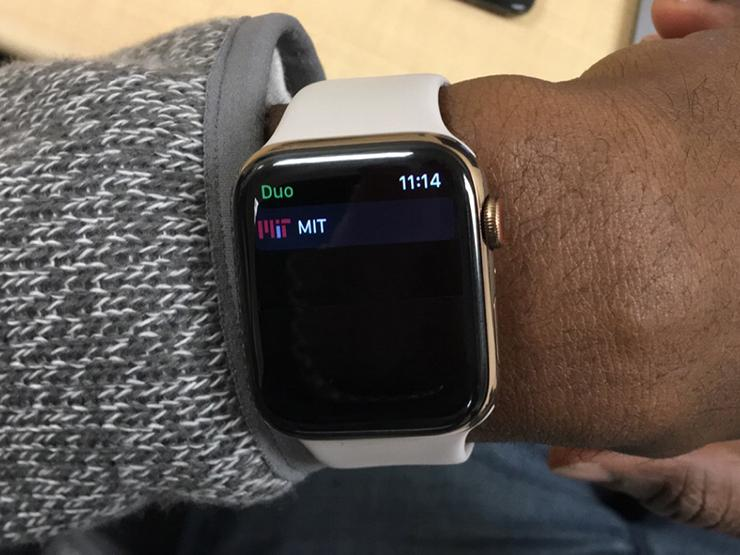 A man's wrist with an Apple Watch displaying the MIT Duo app.