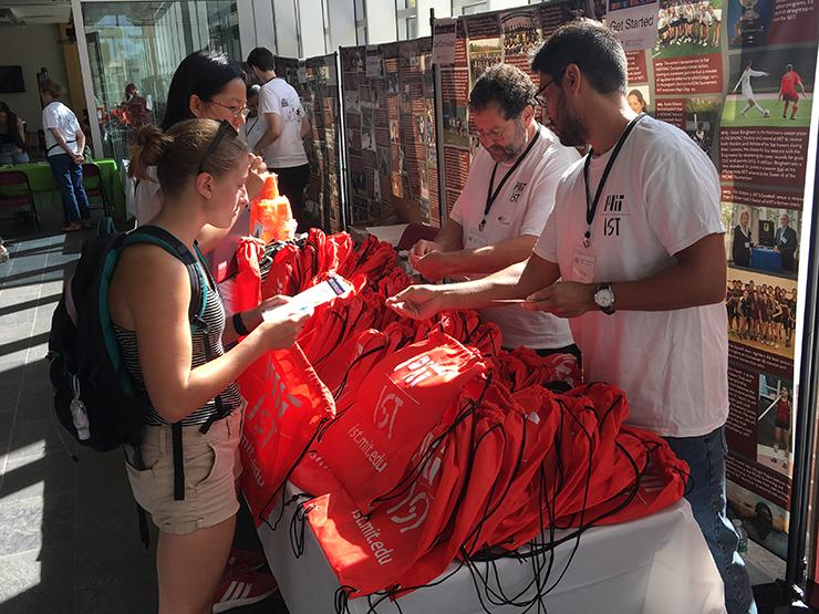 Picture of IS&T staff members handing out red MIT IST swag bags to MIT students.