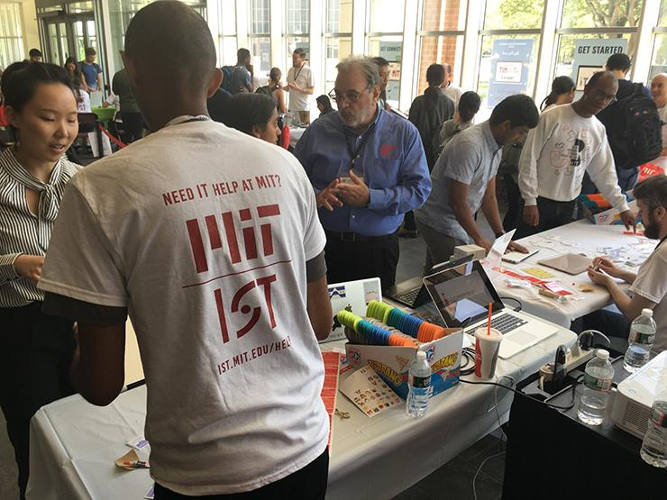 IS&T staffers tagging to students' laptops and tablets in the Z-Center lobby.