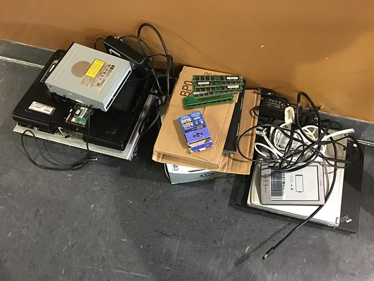 Several piles of old computer hardware on the floor ready for recycling.